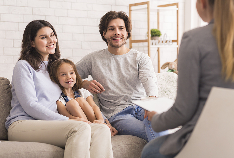 Happy Parents With Little Daughter Sitting Together At Psycholigists Office After Successful Family Therapy